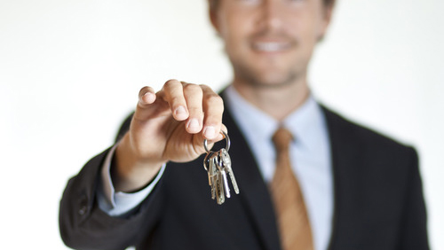 Smiling businessman handing keys